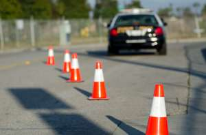 Traffic cones set up to direct traffic around a police car.